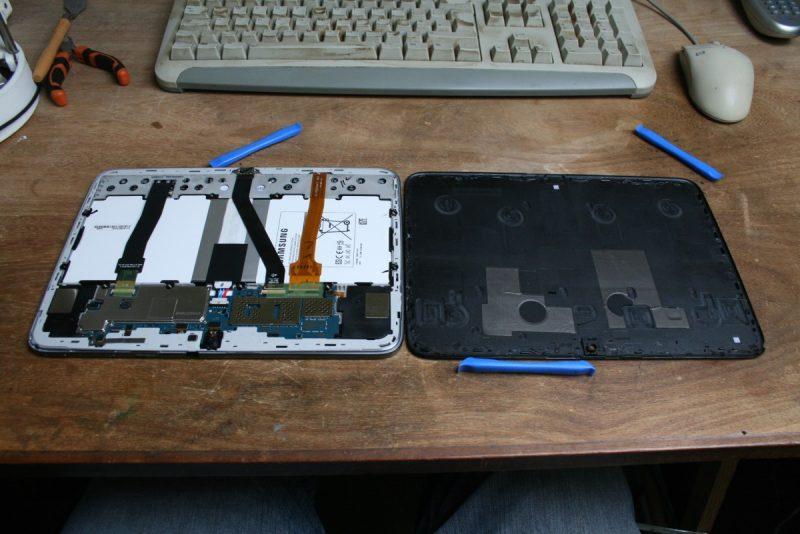 La tablette ouverte révèle les câbles flex qui relie la carte mère à l'écran, à la caméra et au touchscreen.